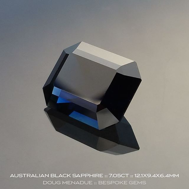 AUSTRALIAN BLACK SAPPHIRE :: 7.05CT :: 12.1x9.4x6.4MM :: Within the depths of this remarkable Australian sapphire you will find the most wonderful and vivid flashes of blue, a deep rich blue that is striking in it's intensity. It is a dark stone and I'd say this sapphire is on the borderline of being a black sapphire. With sapphires, when the colour approahes this sort of depth they can become known as ''black'' sapphires. This beautiful sapphire still retains flashes of the deep rich blue colour especially under lights and when viewed in the hand you can see into the stone and note the blue colour. As you can see, this lovely stone has been made in the Emerald Cut design which is a classic and works well here allowing those striking flashes of blue to really capture the eye.  This black sapphire is part of an old time digger's collection that he built over the years and it now being put up for sale. It has been precision cut and polished locally on the gemfields and is a first class sapphire in every regard. For those folks that have a penchant for dark or black gemstones then this is perfect for you and not to be missed as it is a unique black sapphire. It is very hard to get big beautiful sapphires like this regardless of the colour, especially of this size and quality.  Visit my WHAT'S NEW  page on my website for full details.  DOUG MENADUE  WWW.BESPOKE-GEMS.COM  SYDNEY CBD AUSTRALIA - Precision Gemcutting and Lapidary Services Located In Sydney Australia